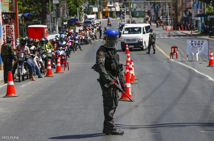 Rendőr áll egy ellenőrző pontnál Manilában 2020. április 2-án.