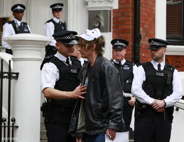 Rendőrök és egy szimpatizáns Ecuador londoni nagykövetségének épülete előtt