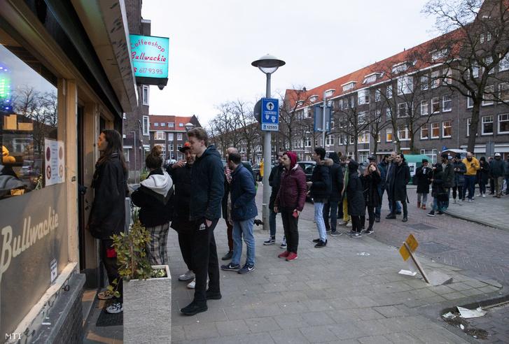 Hosszú sor áll egy marihuánát árusító amszterdami üzlet elõtt 2020. március 16-án miután Bruno Bruins holland egészségügyi miniszter bejelentette hogy az iskolákat a kávézókat az éttermeket és a marihuánaboltokat bezárják a koronavírus terjedése miatt
