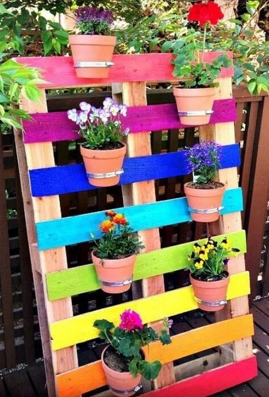 Ez a színpompás virágtartó raklapból van: a cserepeket a színesre festett deszkákra erősítették.