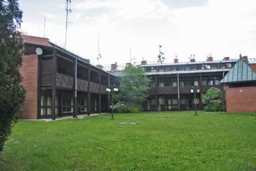 A szálloda a kései szocializmus építészetileg már vonzóbb, regionalista stílusában épült vöröstégla homlokzatokkal és barnára festett fatornácokkal.