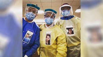 Mosolygós fotót tűznek ki magukról a ruhájukra a védőfelszerelésbe öltözött orvosok
