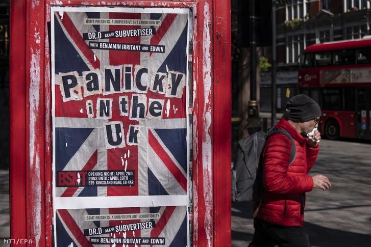Gyalogos sétál egy telefonfülkére ragasztott Pánik az Egyesült Királyságban feliratú plakát előtt Londonban