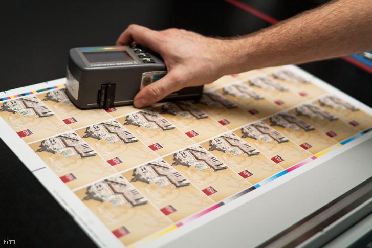 Egy dolgozó egy nyomat színeit ellenőrzi a Magyar Kereskedelmi Bank (MKB) által kibocsájtandó Széchenyi Pihenőkártyák (SZÉP-kártya) gyártása közben a Pénzjegynyomdában