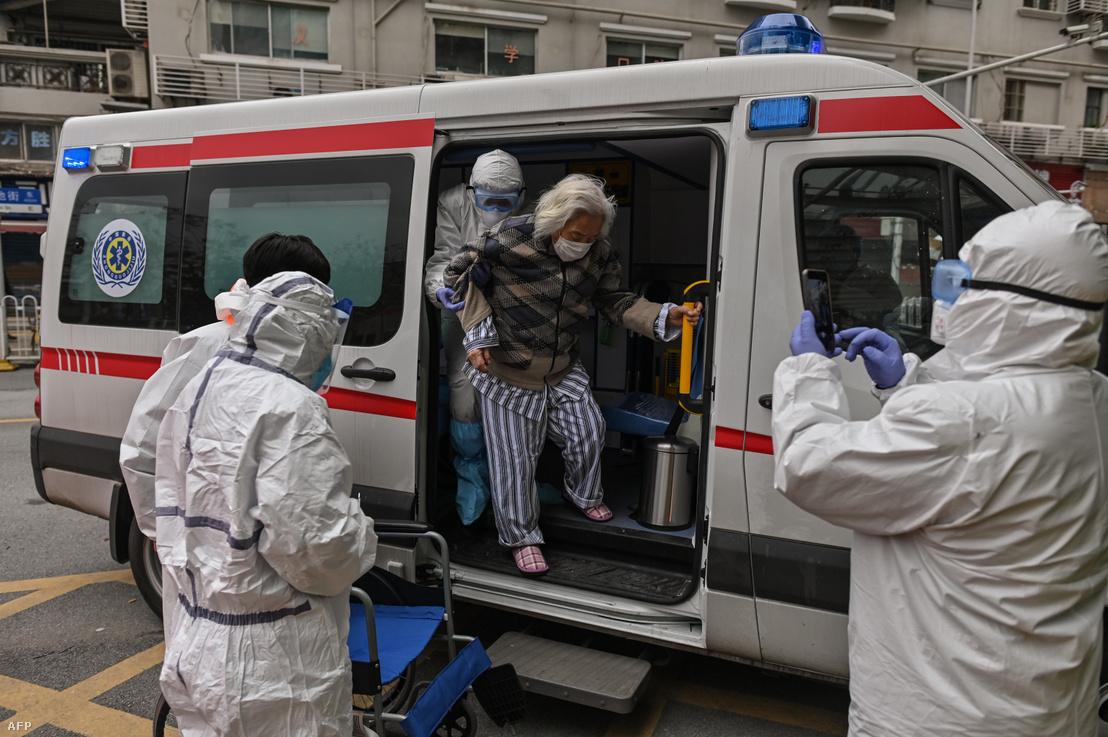Egy idős nőt szállítanak kórházba a mentősök Vuhanban 2020. március 30-án.