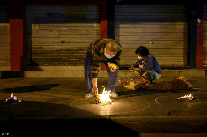 Vuhani lakók papírokat égetnek szeretteik emlékére a csingming, azaz a sírlesöprés ünnepének előestéjén 2020. április 3-án.