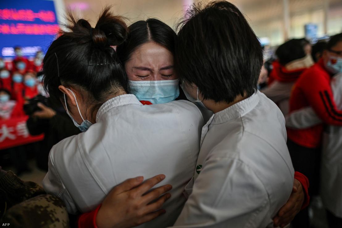A Csilin tartományból érkező orvosi személyzet tagjai és vuhani kollégáik búcsúznak a repülőtéren miután együtt dolgoztak az elmúlt hetekben.