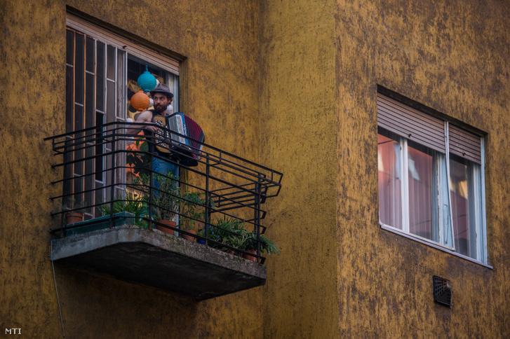 Móser Ádám tangóharmonikán játszik XIII. kerületi otthona erkélyén 2020. március 20-án. Az önkéntes karanténban lévő zenész előadásai és koncertjei a járvány miatt elmaradtak, de otthona erkélyén minden nap 17 órakor minikoncertet ad, amit felesége közvetít a neten.