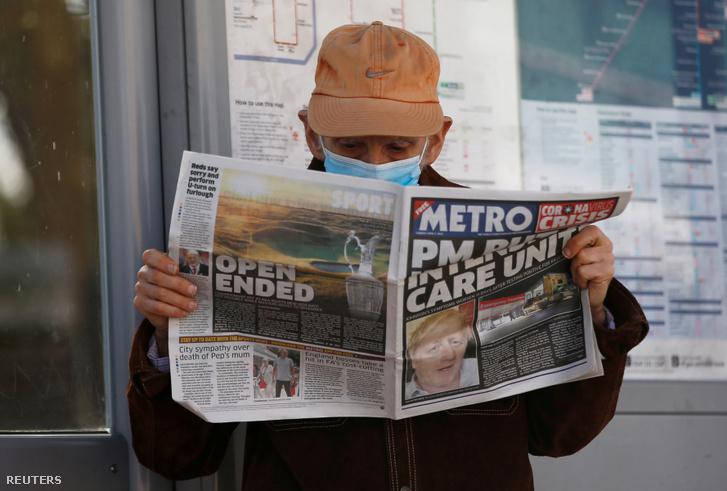 Egy férfi mai újságot olvas a koronavírus hírekkel kapcsolatban a St. Thomas kórház előtt Londonban