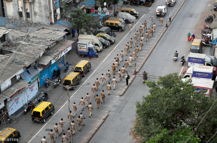 Rendőrök menetelnek az egyik legnagyobb nyomornegyedben Mumbaiban a korlátozó intézkedések meghosszabbítása után 2020. április 11-én