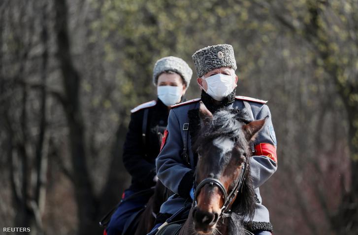 Kozákok járőröznek maszkban lovon a moszkvai Kuszkovo emléktelepen 2020. április 10-én
