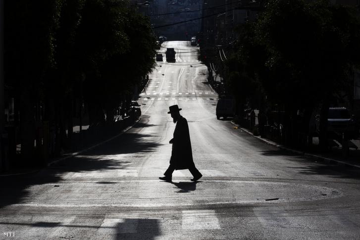 A koronavírus-járvány ellen elrendelt intézkedések miatt néptelen utcán sétál egy ultraortodox zsidó férfi az izraeli Bné-Berakban