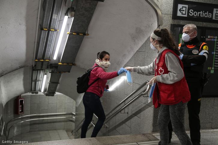 Egy utas maszkot kap a Vöröskereszt munkatársától a barcelonai metró Passeig de Gracia állomásánál