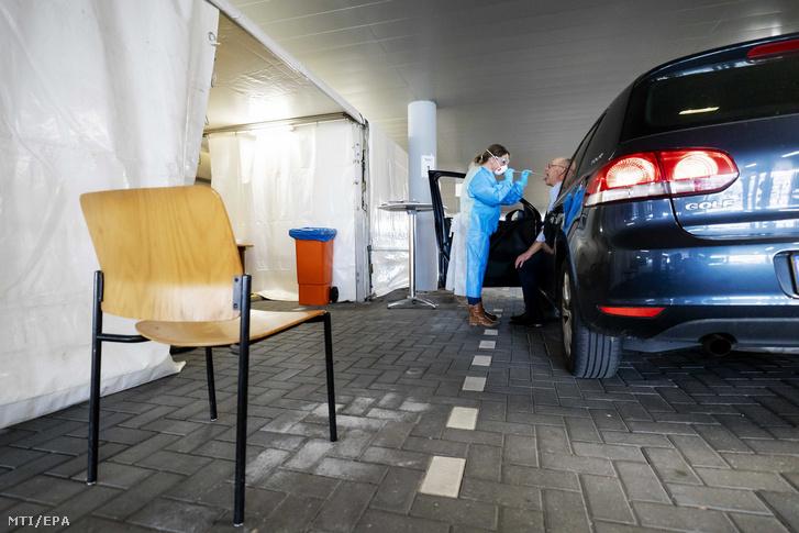 Autós torkából vesz vizsgálati mintát egy egészségügyi dolgozó egy rotterdami utcai tesztelő ponton