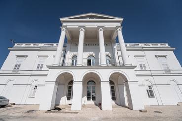 Timpanon és oszlopsor: a klasszicista építészet legjellemzőbb jegyei. Állítólag erről az erkélyről ugratott le lovával Sándor Móric, az Ördöglovas