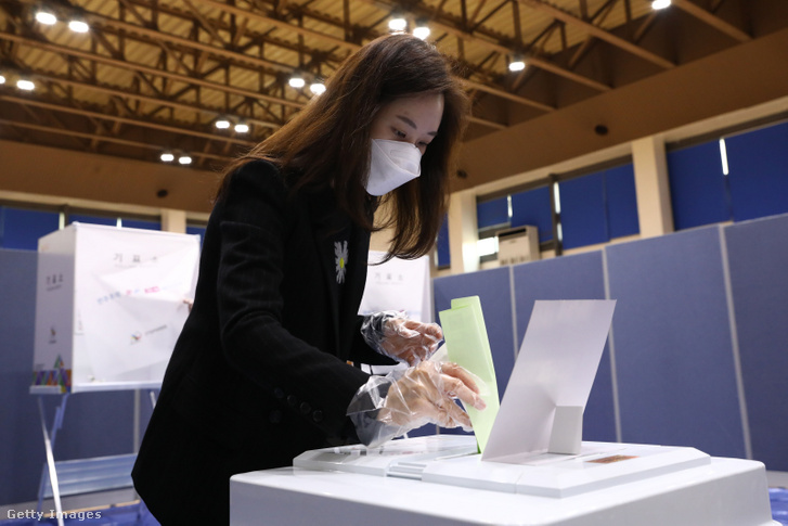 Egy nő leadja szavazatát Szöulban 2020. április 15-én