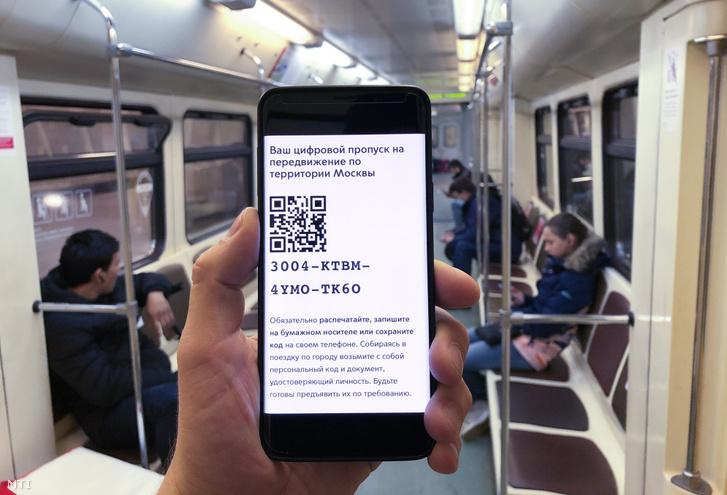 Digitális kódját mutatja az okostelefonján a moszkvai metró egyik utasa 2020. április 14-én.