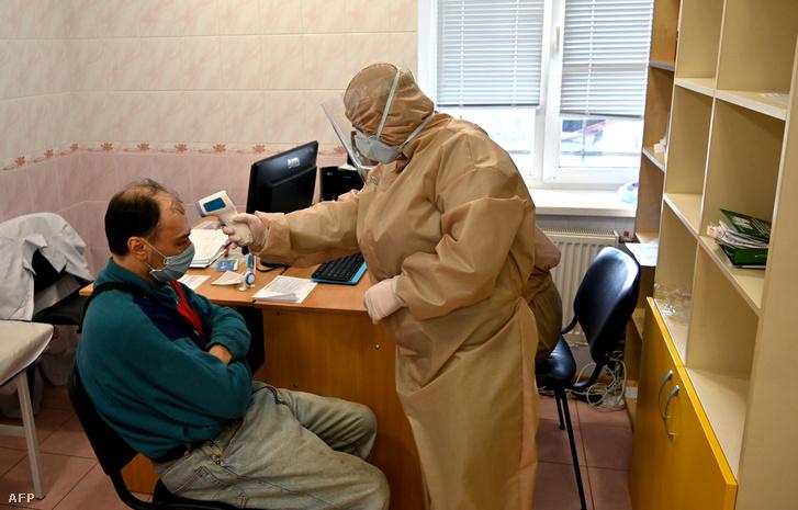 Védőfelszerelést viselő orvos méri egy páciens testhőmérsékletét egy kijevi klinikán 2020. április 15-én.