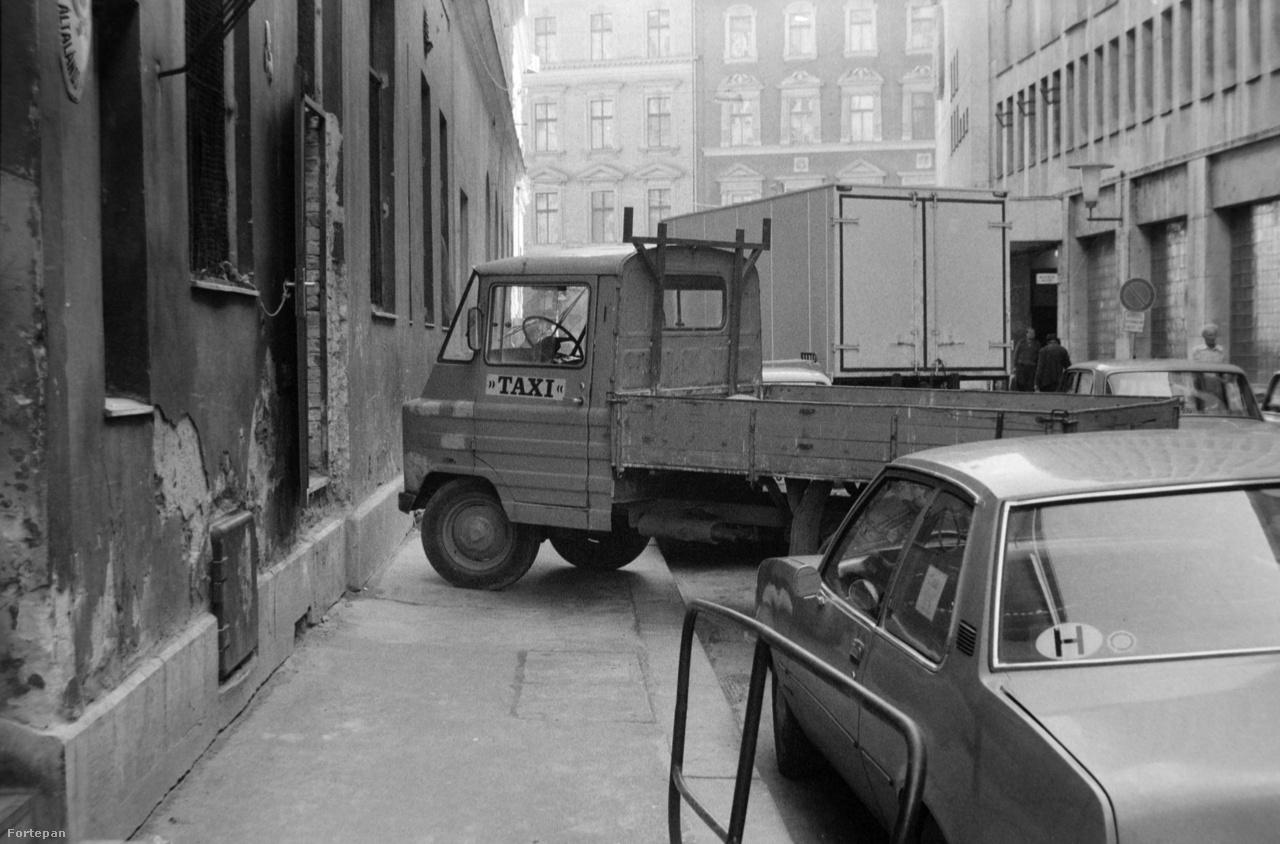 """A tehertaxisok és költöztetők külön kasztot alkottak a 70-80-as évek közlekedésében, külön saját KRESZ-szel. Ennek az volt a lényege, hogy mivel árut pakoltak, hoztak vagy éppen vittek, ők teljes joggal elfoglalhatták az egész járdát. A képen a VII. kerületi Osvát utcában épp egy jeles képviselőjük, egy """"mindenes"""" Zsuk kisteherautó pihen a járdán kirakodva."""