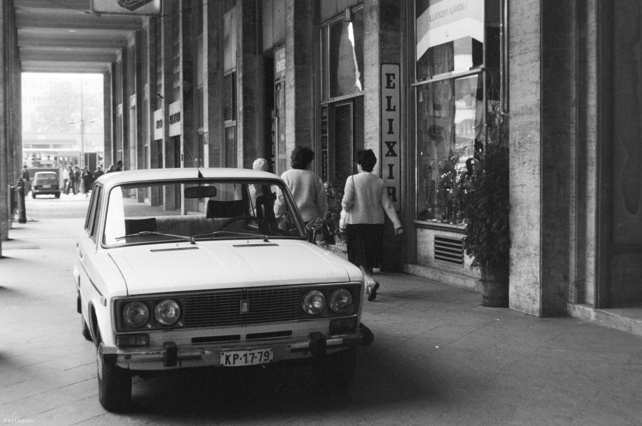 1980-ban az egyik közép-felső kategóriás gépkocsinak számított a Lada 1600-os. Gyakran vállalati autónak használták, és a mindenható igazgató elvtárs sofőrje sok mindent megengedhetett magának, csak úgy, mint a kor kisvállalkozójának számító gazdag maszek, akik körében szintén divatos volt a szocialista BMW-nek is nevezhető márka. A képen sejthetően az Elixír illatszerbe ugrott be a kocsi gazdája, a lehető legpöffeszkedőbb módon parkolva. Méghozzá pont annak a Madách térnek az árkádjai alatt, ahol pár évvel azelőtt megjelent az első pesti parkolóautomata.