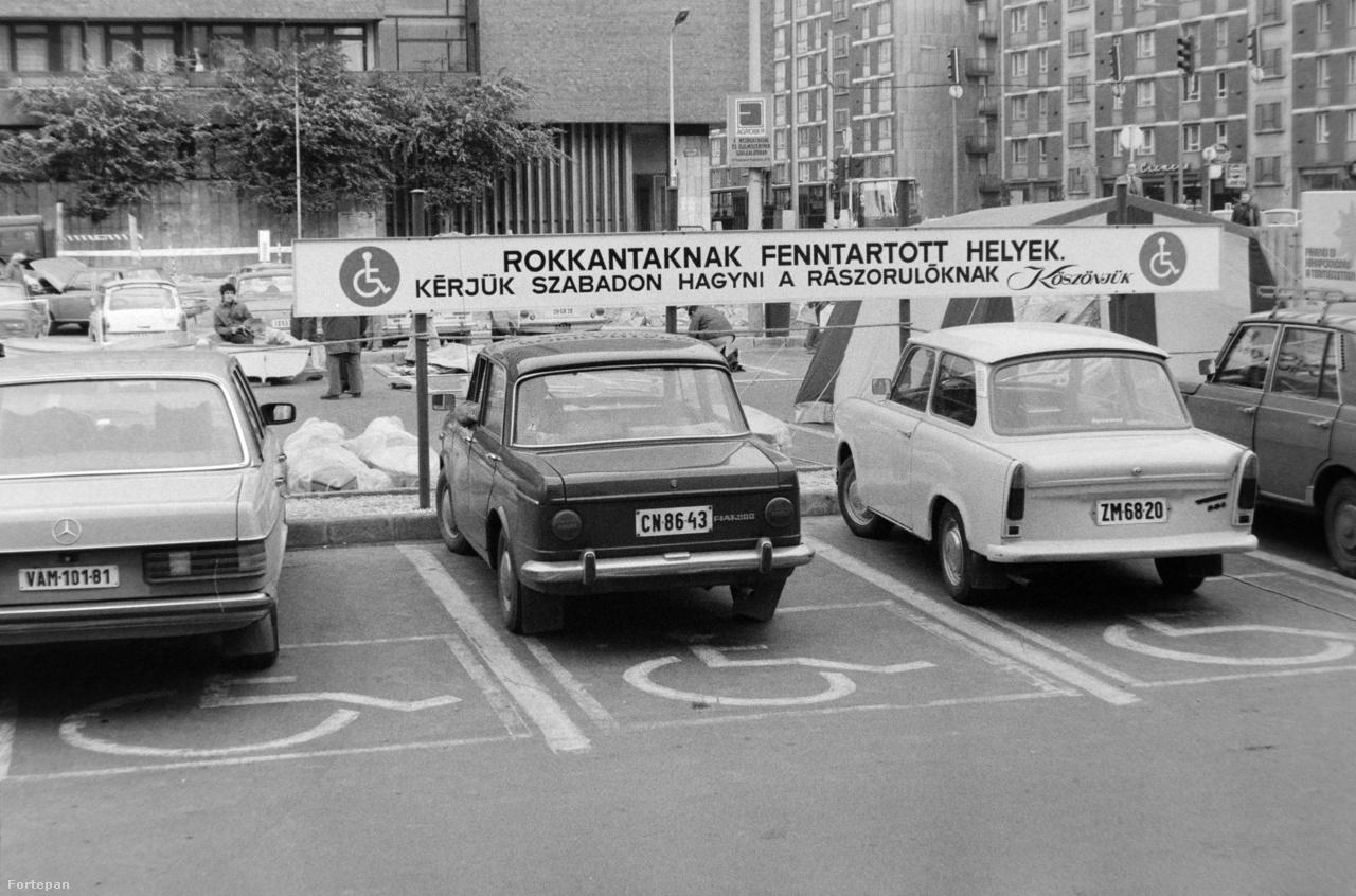 """A mozgássérültek parkolási nehézségeire is aránylag hamar megpróbáltak megoldást találni Budapesten, váltakozó sikerrel. Csakúgy mint mostanában, a mozgássérült parkolóhelyet gyanúsan sok gépkocsi használja, mint gyakran kiderült, jogszerűtlenül. 1981-ben, a Budai Skála parkolójában is gyanús módon gyorsan teleparkolták a """"rokkantaknak fenntartott helyeket"""", az udvarias felszólítás ellenére."""