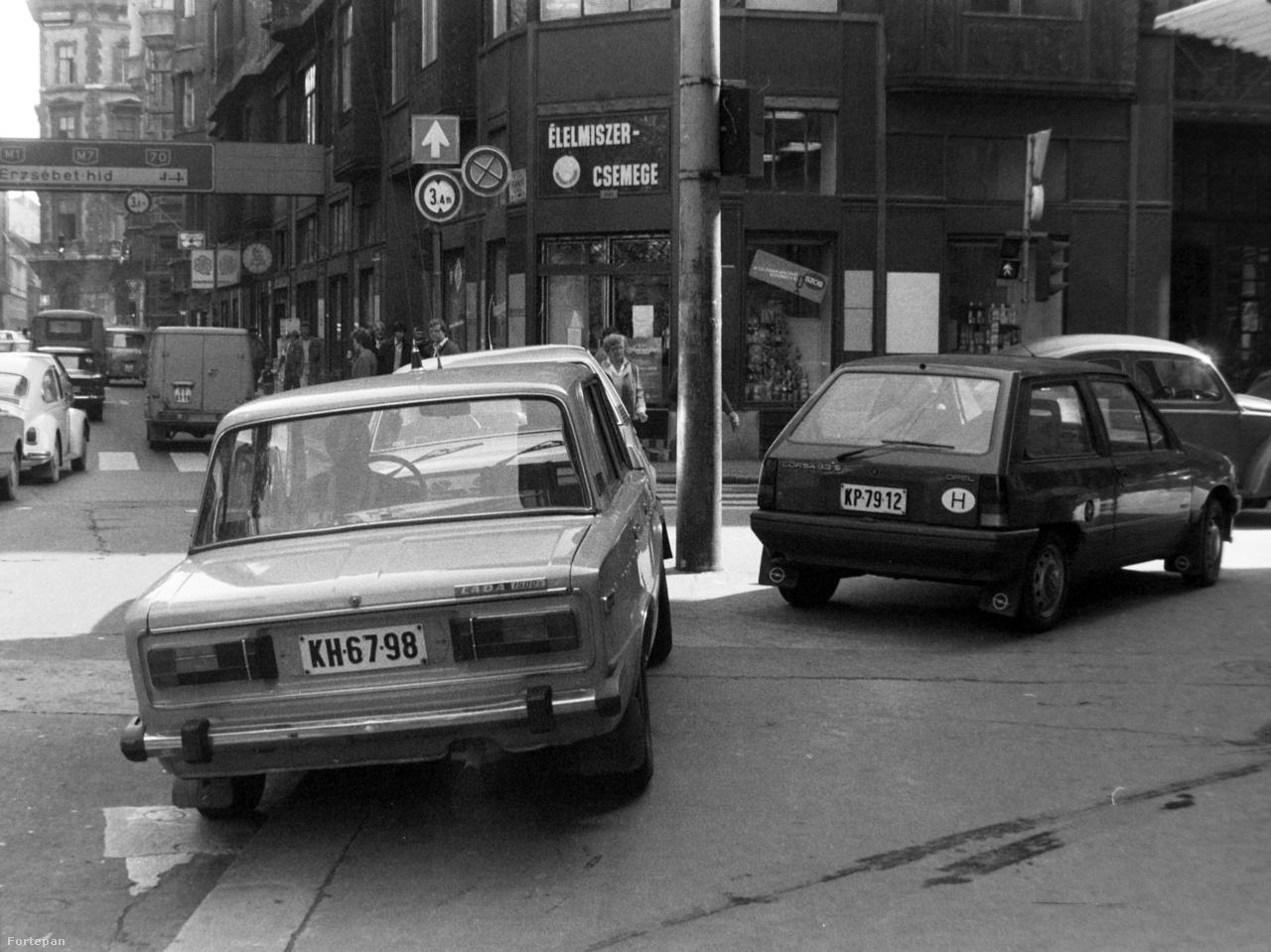 Minél több lett az autó Budapesten, annál kevesebb lett a parkolóhely. A közlekedőknek egy új típusa fejlődött ki: a bunkó autós, aki magasan tojt mindenféle KRESZ-szabályra, vagy arra, hogy akadályozza a gyalogosokat a mozgásban a járdán. A Kossuth Lajos utca - Városház utca sarkán szabályosan elbarikádozták a zebrát, ami jól látszik ezen az 1985-ös fotón.