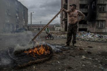 Egy roma férfi rugós matracot éget a fallal leválasztott Horea utcai gettóban, 2013