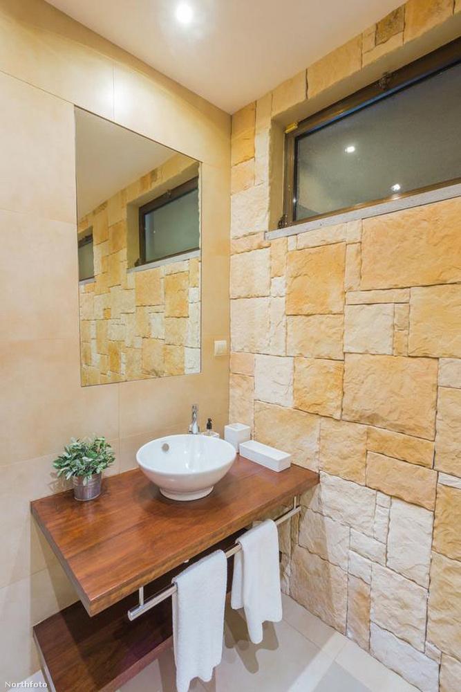 Fürdőből sincs hiány, a falon lévő kőborítás és a mosdó alatti faasztalka is tovább erősíti a mediterrán stílust
