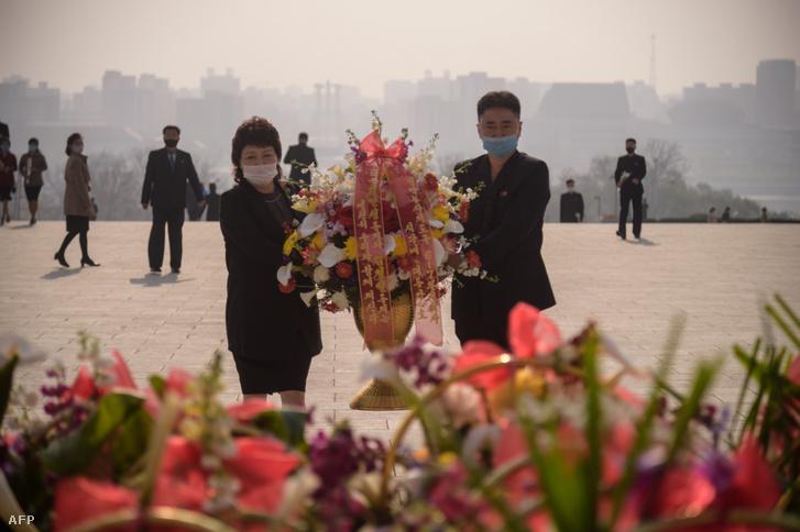 Maszkot viselő észak-koreaiak helyeznek el koszorút Kim Ir Szen és Kim Dzsong Il koreai vezetők szobránál Phenjanban 2020. április 15-én, Kim Ir Szen születésnapján