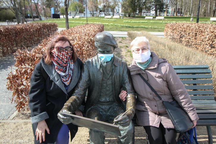 Két, maszkot viselő idős nő a festő Antoni Suchanek maszkos szobra mellett Gdyniában, 2020. április 16-án