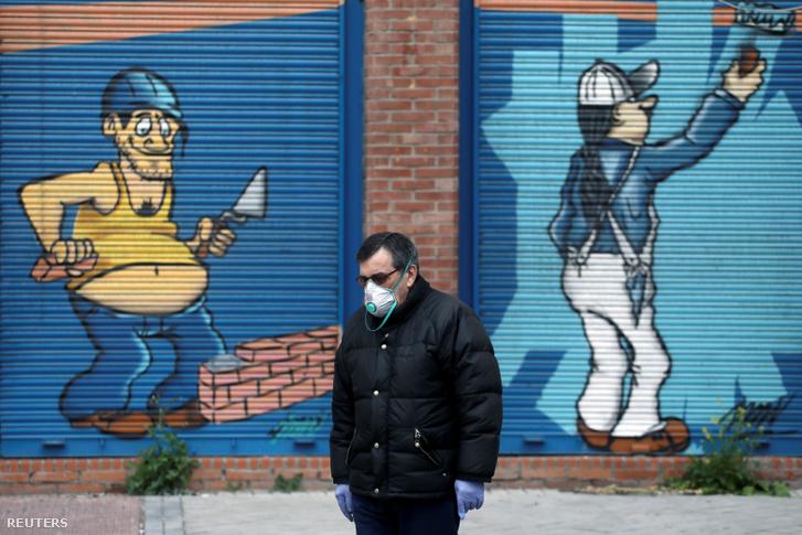 Egy ember sétál arcmaszkban a koronavírus miatt bezárt üzletek előtt Madridban 2020. április 14-én