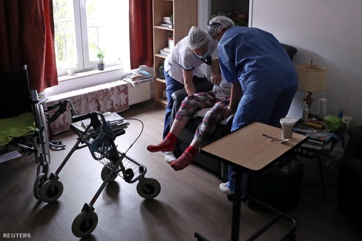 Gondozók segítenek Brüsszel (Belgium) Jette régiójában lévő Christalain Idősek Otthona egyik lakójának 2020. április 13-án