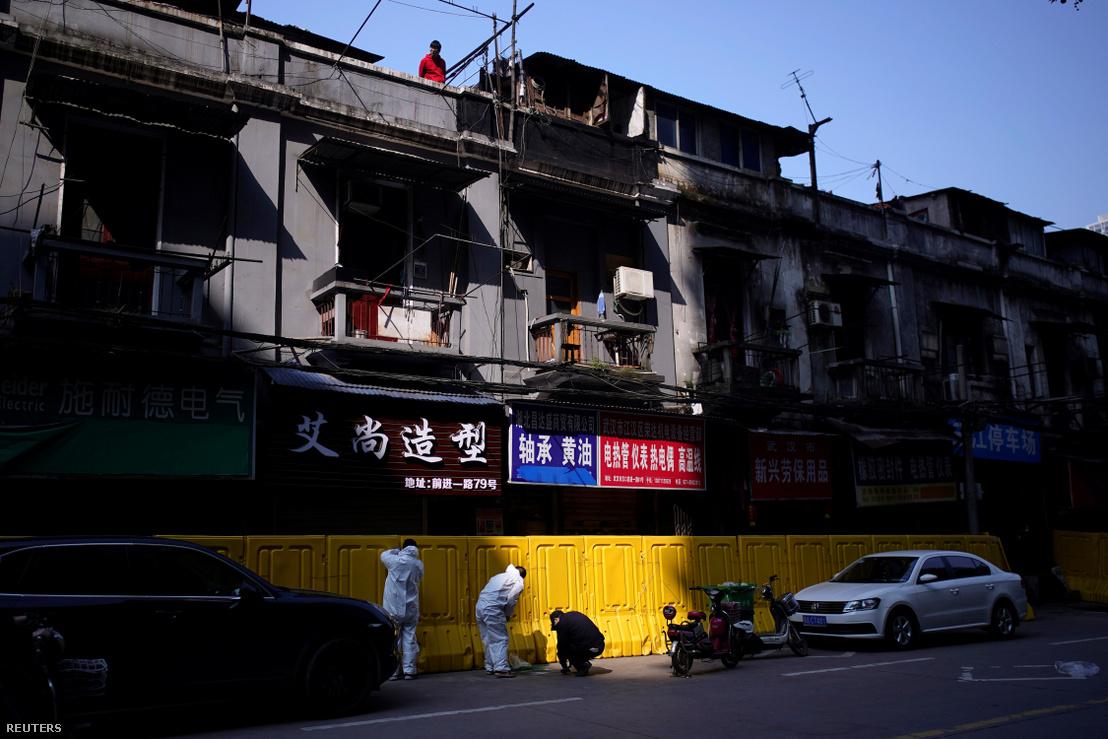 Védőöltözetet viselő munkások bontják el a koronavírus-járvány miatt felállított műanyag falakat, amivel a lakókat szeparálták el egymástól a kínai Vuhanban 2020. április 12-én. Hupej tartomány fővárosa volt a járvány kirobbanásának első gócpontja.