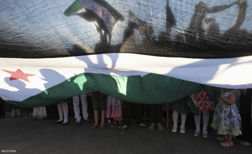 Szíriai menekültek és helyiek tüntetnek ellenzéki zászlóval Jordániában. Az ENSZ legújabb jelentése szerint több mint százezer szíriai menekült el az országból augusztusban, ami a legmagasabb egy hónapra eső szám a konfliktus kezdete óta.