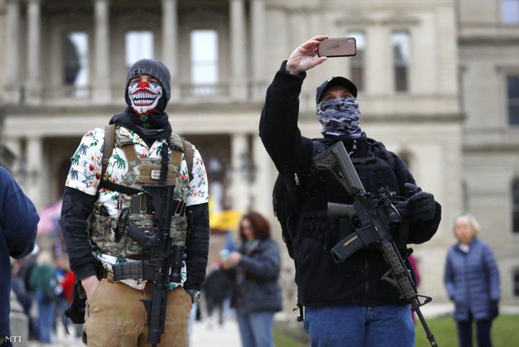 Két gépfegyveres férfi a koronavírus-járvány miatt bevezetett korlátozó intézkedésekkel elégedetlen emberek között Michigan állam törvényhozásának épülete előtt Lansingban 2020. április 15-én.