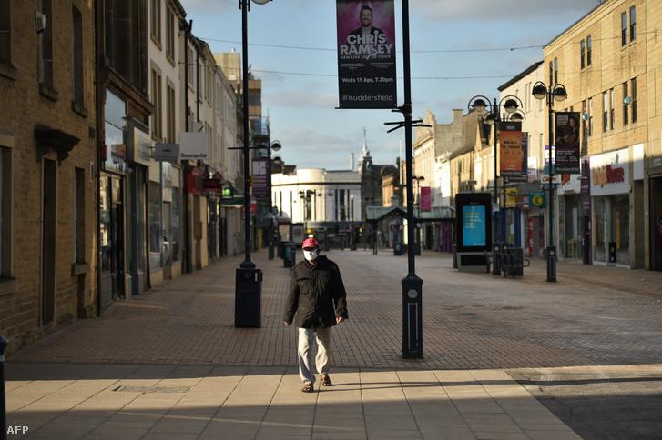 Gyalogos sétál a bezárt boltok között Huddersfieldben 2020. április 17-én