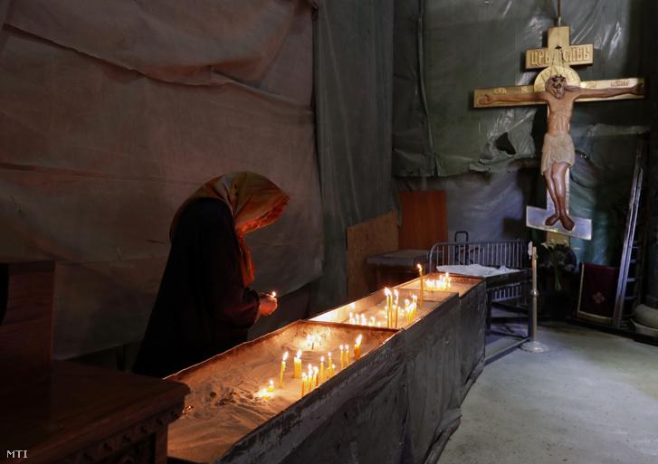 Gyertyát gyújt egy nő a belgrádi Szent Száva-templom szerb ortodox templomban húsvét alkalmából 2020. április 16-án