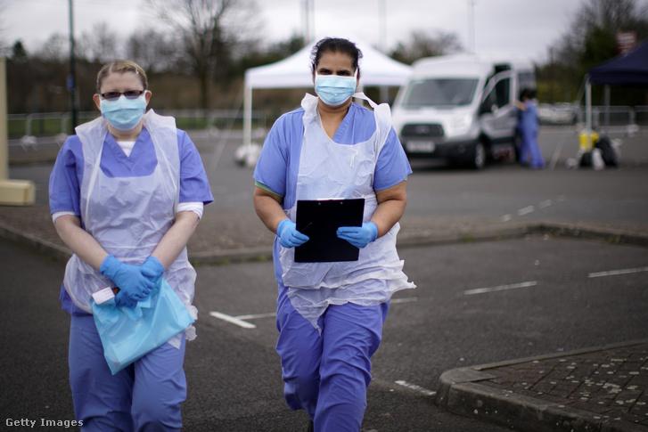 Nővérek várakoznak a következő páciensre a wolverhamptoni áthajtásos (drive through) koronavírus tesztelő állomáson 2020. márciu 12-én