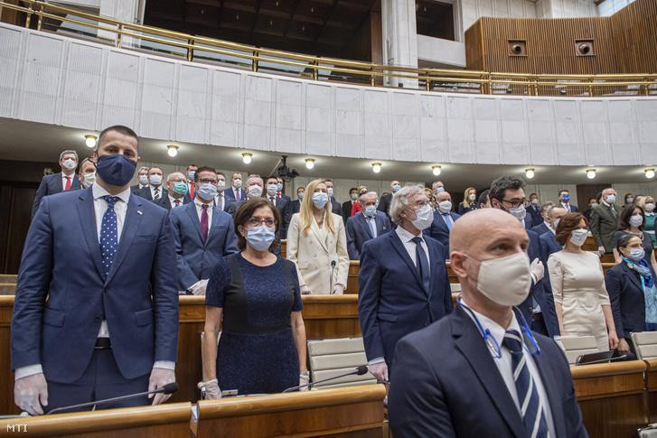 Az új koronavírus járványa miatt védőmaszkot és gumikesztyűt viselő képviselők a parlament alakuló ülésén a pozsonyi ülésteremben 2020. március 20-án