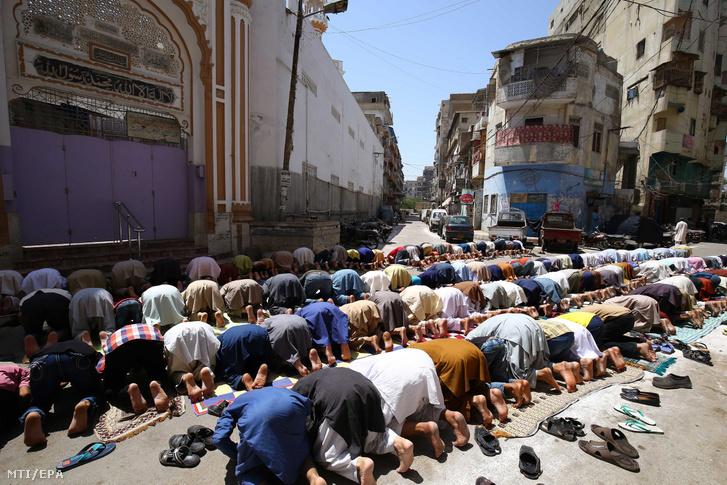 A koronavírus-járvány miatt elrendelt helyi kijárási korlátozás ellenére a pénteki imájukat végzik muzulmán hívők a pakisztáni Karacsi egyik bezárt mecsetje előtt 2020. április 17-én.