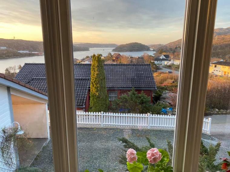 Linda nappalijának ablakából tipikus norvég táj tűnik fel skandináv házikókkal és az erdővel borított dombokat átszelő tenger egy nyúlványával
