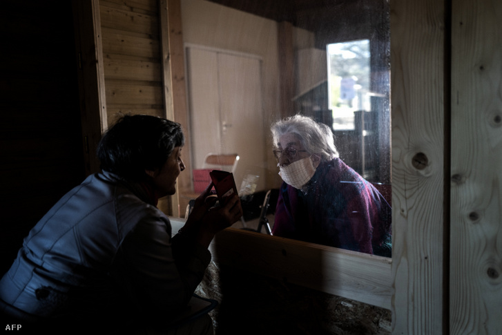 Egy nő beszél édesanyjával és mutat neki egy képet a Roche-La-Moliere-ban található idősotthonban Franciaországban 2020. április 15-én