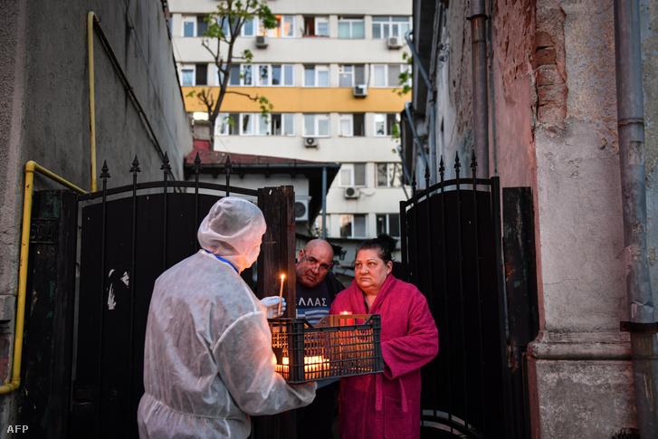Védőruhába öltözött egyházi önkéntes adja oda a szent fényt az ortodox húsvétot otthonukban ünneplőknek Bukarestben 2020. április 18-án