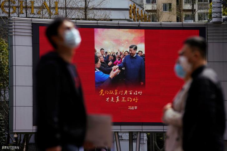Gyalogosok sétálnak el egy sanghaji kijelző előtt, amin Hszi Csin-ping kínai elnök látható 2020. március 23-án