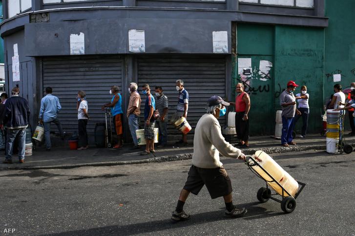 A járvány miatt maszkot viselő emberek állnak sorba vízért Venezuela fővárosában, Caracasban 2020. március 21-én