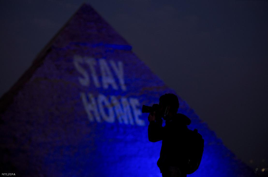A Maradj otthon feliratot vetítik az egyik kék fénnyel megvilágított piramisra Gízában
