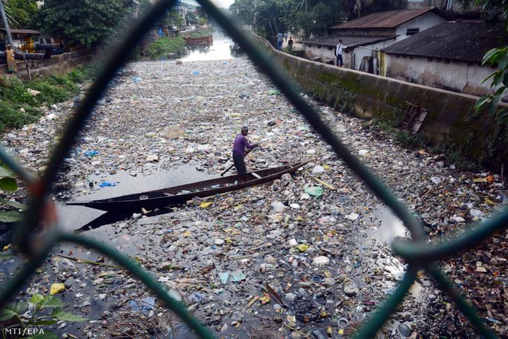 Műanyagpalackokat és más újrahasznosítható tárgyakat gyűjt egy férfi csónakjába a Baralu folyó szeméttel teli vízéből Északkelet-Indiában