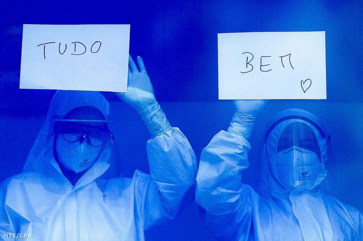 Védőruhát viselő egészségügyi dolgozók a Minden rendben feliratot mutatják a helyi kórház ablakából a munkájukat megköszönő embereknek a portugáliai Braga városban.