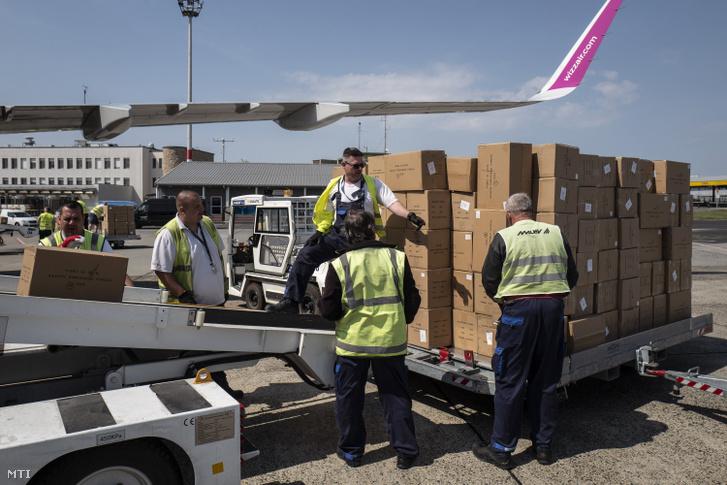 A Kínából érkezett egészségügyi védőfelszerelés-szállítmányt pakolják ki a Liszt Ferenc-repülőtéren 2020. április 18-án.