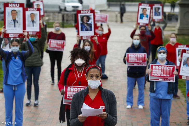 Az amerikai hivatásos ápolók legnagyobb szakmai szervezetének tagjai koronavírus-fertőzésben elhunyt munkatársaikat ábrázoló plakátokkal tüntetnek a washingtoni Fehér Ház előtt 2020. április 21-én